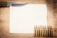 Carta in bianco, coltello e pallottole Immagini Stock