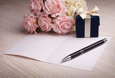 Carta in bianco con i fiori ed il regalo Fotografie Stock