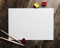 Carta in bianco con l'acquerello e spazzole sulla tavola di legno per i modelli Fotografie Stock Libere da Diritti