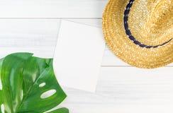 Carta in bianco del Libro Bianco sulla vista di legno del piano d'appoggio con il cappello di paglia e Fotografia Stock