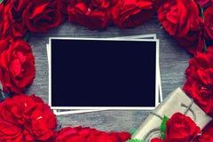 Carta in bianco della foto nel telaio fatto dei fiori delle rose rosse e del contenitore di regalo Fotografia Stock