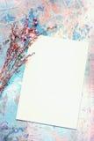 Carta in bianco e fiori secchi su vecchio Backgroun di legno dipinto Immagine Stock