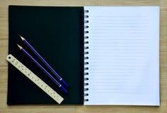 Carta in bianco e matite sulla vista da tavolo di legno Immagini Stock