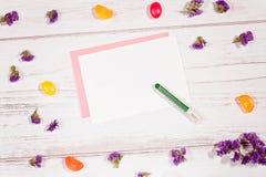 Carta in bianco e pastello su fondo bianco con i fiori lilla e le caramelle variopinte Fotografia Stock