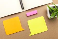Carta in bianco, libro, penna e pianta su fondo marrone immagine stock libera da diritti