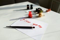 Carta calligrafica piacevole con l'iscrizione rossa ti amo su bianco Fotografie Stock