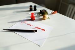 Carta calligrafica piacevole con l'iscrizione rossa ti amo su bianco Fotografia Stock