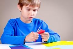 Carta colorata di taglio del bambino con le forbici alla tavola fotografie stock
