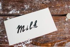 Carta con il latte di parola sulla disposizione del piano della tavola Immagini Stock