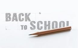 Carta con la parola DI NUOVO dell'iscrizione ALLA SCUOLA vicino alla matita di legno Fotografia Stock Libera da Diritti