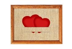 Carta d'annata del biglietto di S. Valentino sotto forma di cuori di carta rossi su tessuto Fotografia Stock