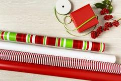 Carta da imballaggio semplice e moderna e nastro rossi e verdi del regalo di Natale con le decorazioni naturali Fotografie Stock Libere da Diritti