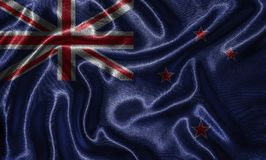 Carta da parati dalla bandiera della Nuova Zelanda e dalla bandiera d'ondeggiamento da tessuto fotografie stock