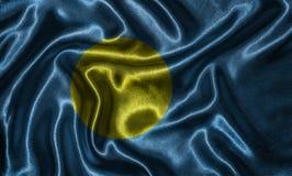 Carta da parati dalla bandiera di Palau e dalla bandiera d'ondeggiamento da tessuto fotografia stock