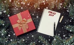 Carta da parati delle vacanze invernali su fondo di legno nero Cartolina d'auguri di natale con luce ed effetto della neve Letter fotografie stock libere da diritti