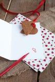 Carta de amor con las galletas de la dimensión de una variable del corazón y la pluma roja Imagen de archivo