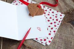 Carta de amor con las galletas de la dimensión de una variable del corazón, y pluma roja Fotos de archivo