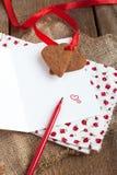 Carta de amor con las galletas de la dimensión de una variable del corazón, y pluma roja Fotografía de archivo libre de regalías