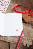 Carta de amor con las galletas de la dimensión de una variable del corazón, y pluma roja Imagenes de archivo