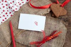 Carta de amor con las galletas de la dimensión de una variable del corazón, y pluma roja Fotos de archivo libres de regalías
