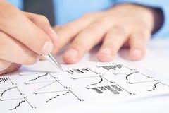 Carta de barra do desenho do homem de negócios e o outro infographics na almofada de nota Imagens de Stock Royalty Free
