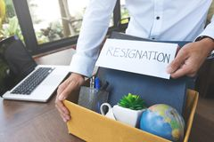 Carta de demissão da terra arrendada do empregado e embalagem de uma caixa para sair do escritório imagem de stock royalty free