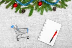 Carta de la Navidad Ramas del abeto y conos del pino, bolas en el fondo de madera blanco del thr con las decoraciones Saludos del imagen de archivo