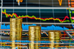 Carta de la tendencia bajista y pilas financieras de monedas de oro imagen de archivo libre de regalías