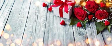Carta dei biglietti di S. Valentino - contenitore e rose di regalo sulla Tabella di legno immagine stock