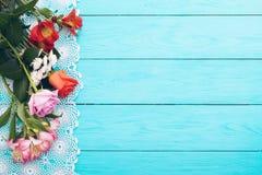 Carta dei fiori e della tovaglia del pizzo su fondo di legno blu Vista superiore e fuoco selettivo Copi lo spazio Derisione su Bi immagine stock