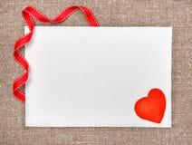 Carta del biglietto di S. Valentino con estrarre cuore rosso su tela da imballaggio Immagini Stock