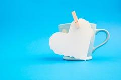 Carta del cuore tagliata sulla tazza blu Immagine Stock