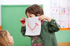 Carta della tenuta del ragazzo con il sorriso attinto  Fotografia Stock