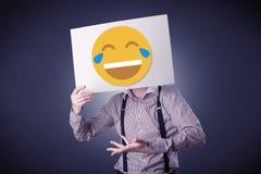 Carta della tenuta dell'uomo d'affari con l'emoticon di risata Immagini Stock