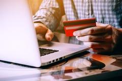 Carta di credito asiatica della tenuta del giovane e computer portatile di battitura a macchina f della tastiera Immagini Stock Libere da Diritti