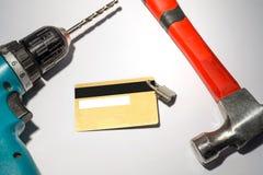 Carta di credito con il trapano ed il hummer d'attaccatura Immagini Stock