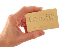 Carta di credito dell'oro della holding della mano con testo su bianco Immagini Stock