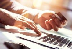 Carta di credito della mano della tenuta dell'uomo del primo piano Compera di pagamenti di Use Laptop Online dell'uomo d'affari G Immagine Stock