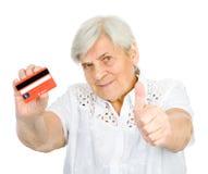 Carta di credito della tenuta della donna con i pollici su. sguardo Fotografia Stock Libera da Diritti