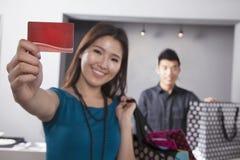 Carta di credito della tenuta della giovane donna al deposito di modo fotografia stock