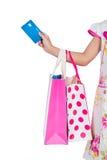 Carta di credito della tenuta della mano del ` s del bambino e sacchetti della spesa variopinti Fotografia Stock