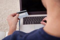 Carta di credito della tenuta della persona facendo uso del computer portatile Fotografia Stock