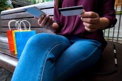 Carta di credito della tenuta della donna e smartphone usando per il onli di compera fotografie stock