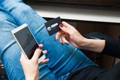 Carta di credito della tenuta femminile della mano e smartphone di plastica usando Immagini Stock