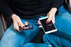 Carta di credito della tenuta femminile della mano e smartphone di plastica usando Immagini Stock Libere da Diritti