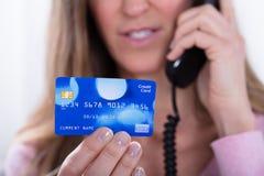 Carta di credito della tenuta della mano del ` s della donna mentre parlando sul telefono fotografie stock libere da diritti