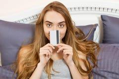 Carta di credito della tenuta della ragazza che si trova a letto Giovane donna che fa spesa online attraverso il PC della compres immagini stock libere da diritti