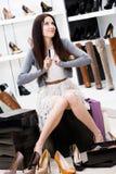 Carta di credito delle mani della femmina nel negozio delle calzature Immagini Stock