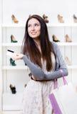 Carta di credito delle mani della giovane donna nel negozio delle calzature Immagini Stock Libere da Diritti