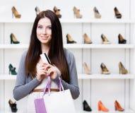 Carta di credito delle mani di signora nel negozio delle calzature Immagine Stock